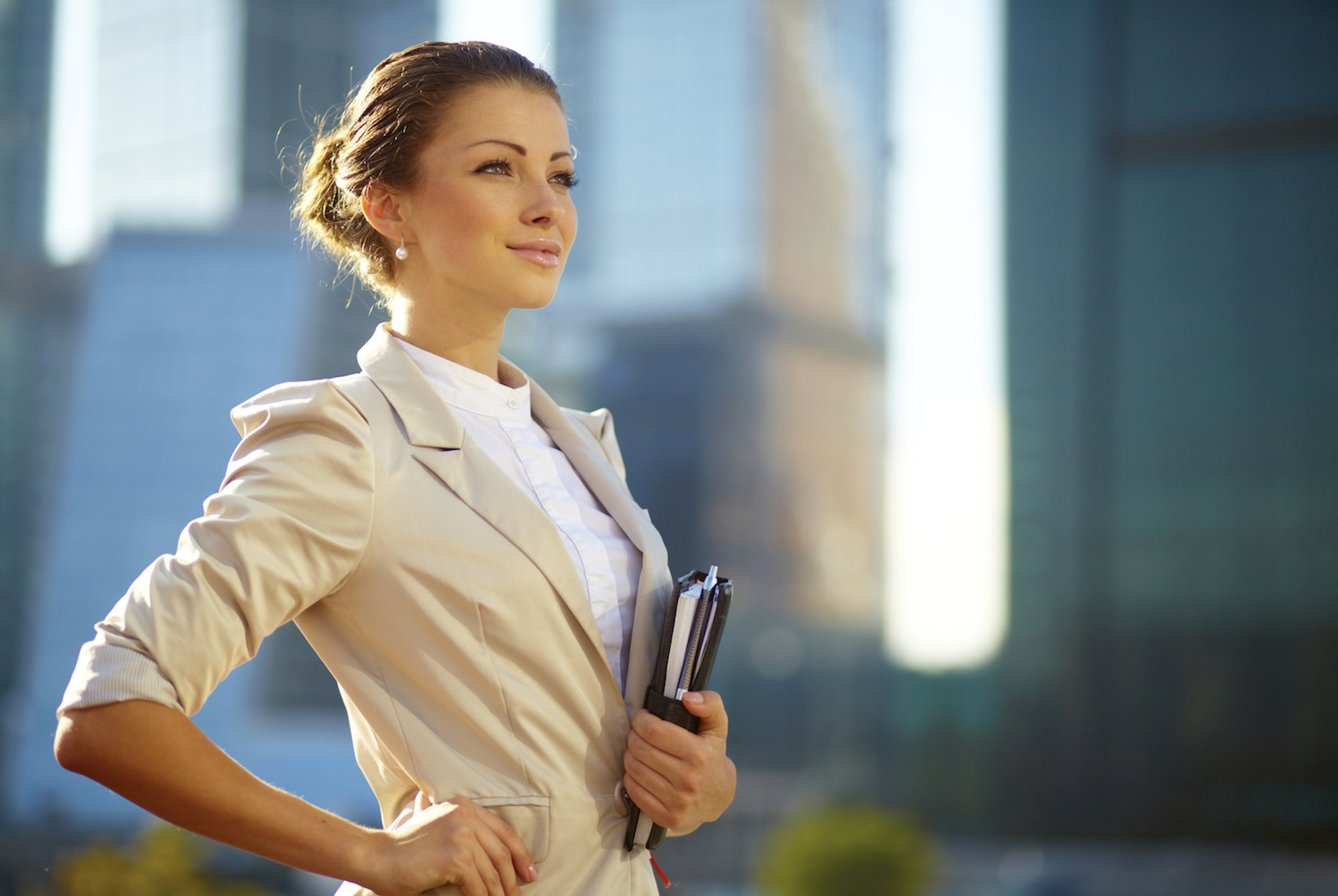 Portrait of cute young business woman outdoor over building background