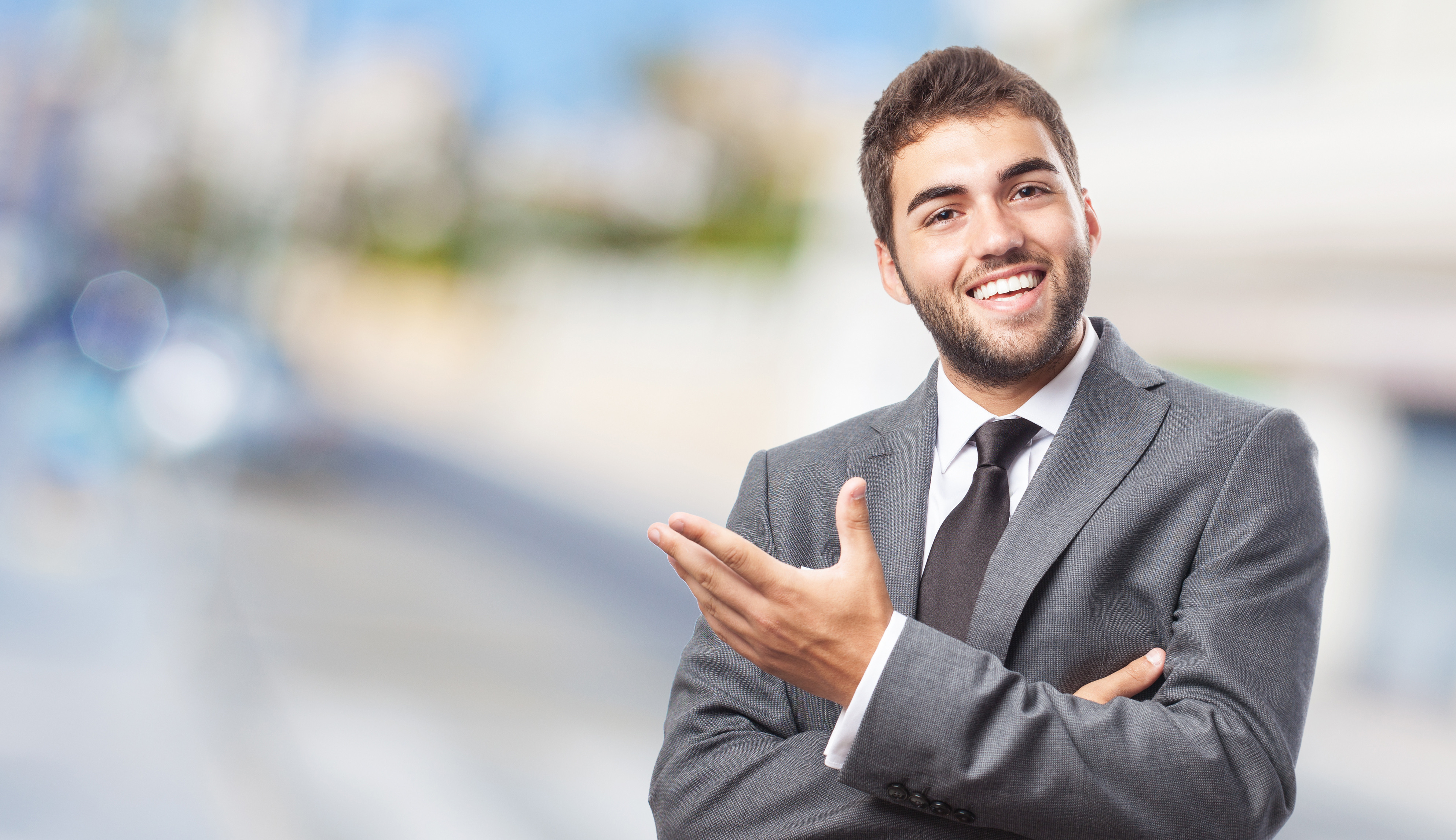 handsome young successful man doing a welcome gesture